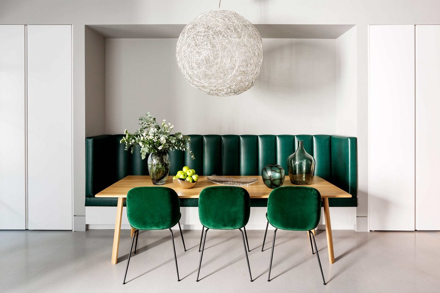 green leather banquette with green velvet chairs